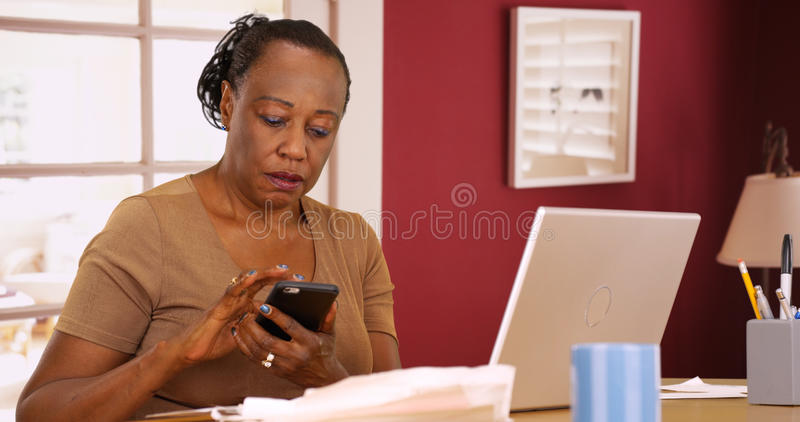 Une femme de couleur plus âgée utilise son téléphone et ordinateur portable pour faire ses impôts images stock