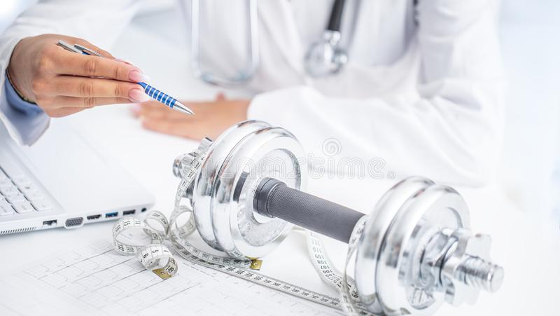 Une femme de docteur dans les cabinets de consultation prescrit le mouvement et la perte de poids de sport utilisant des haltères photos stock