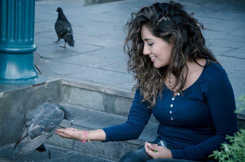 Une femme de sourire alimentant un pigeon de sa main image stock