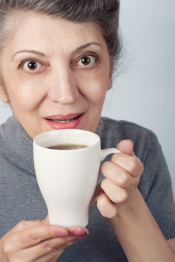 Une femme de sourire plus âgée tenant la tasse de thé photo libre de droits