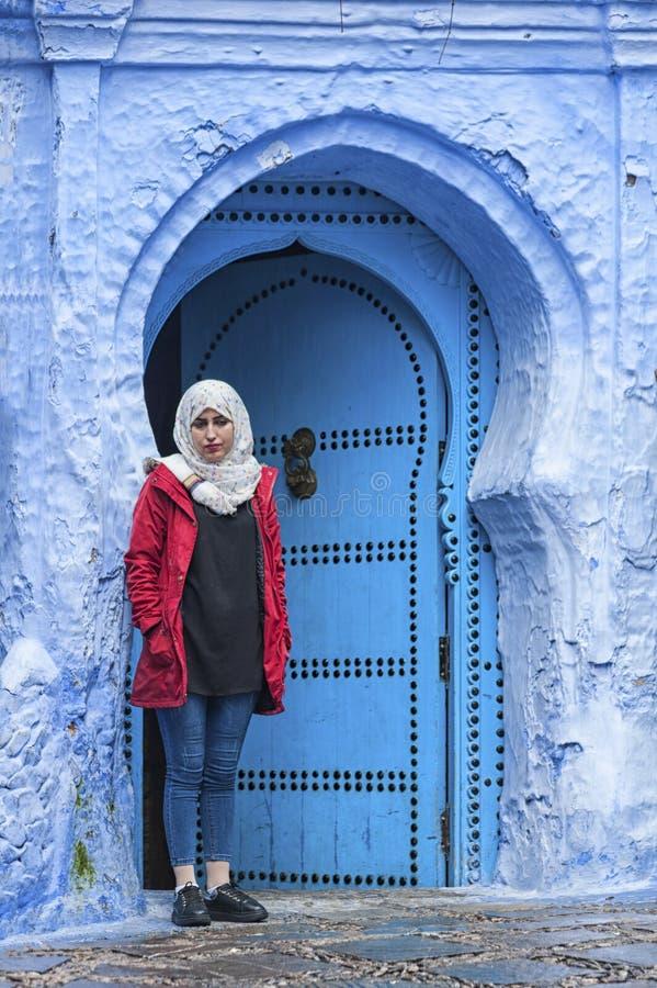 Une femme devant une porte marocaine typique, Chefchaouen Maroc photographie stock