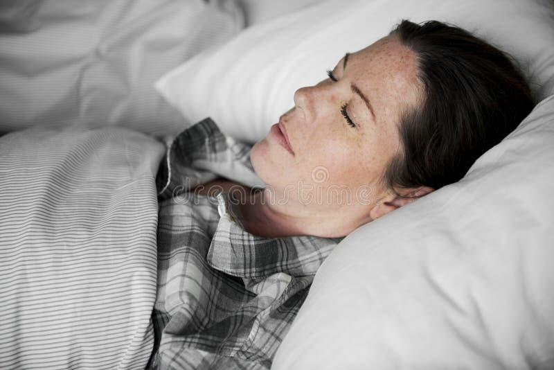 Une femme dormant solidement sur le lit images libres de droits