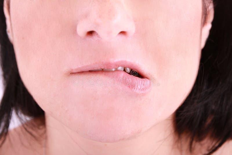 Une femme embarrassed mordant sur sa languette photo libre de droits