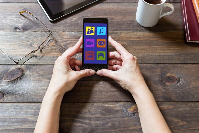 Une femme emploie les réseaux sociaux avec un téléphone portable image stock