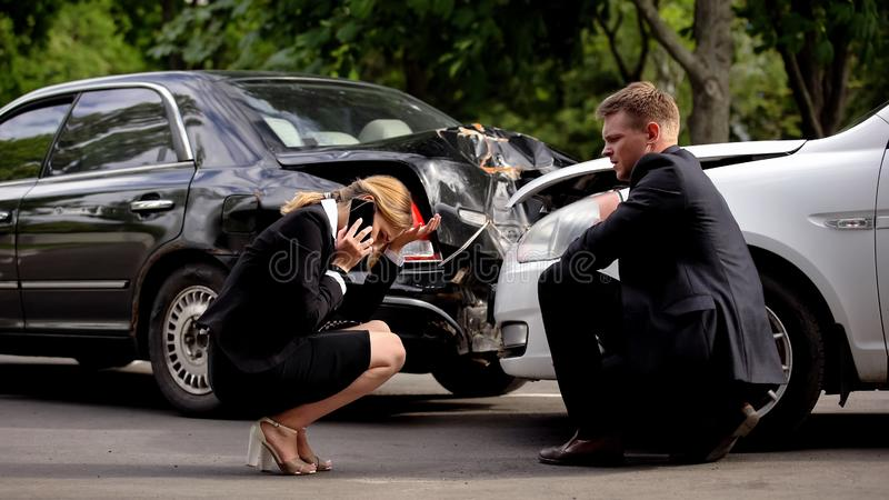 Une femme en état de stress appelle la police près de voitures écrasées, collision, assurance images stock