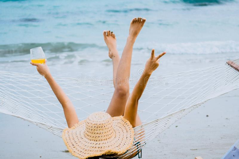 Une femme en maillot de bain se relaxer allongée sur un hamac sur la plage images stock