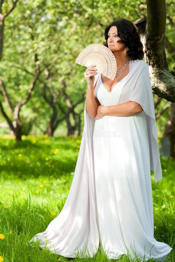 Une femme en parc tient une fan images stock