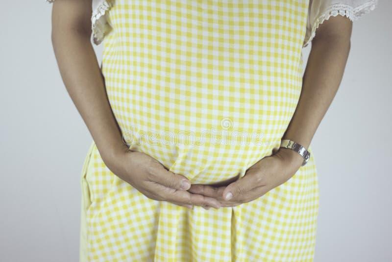 Une femme enceinte avec remet le ventre image stock