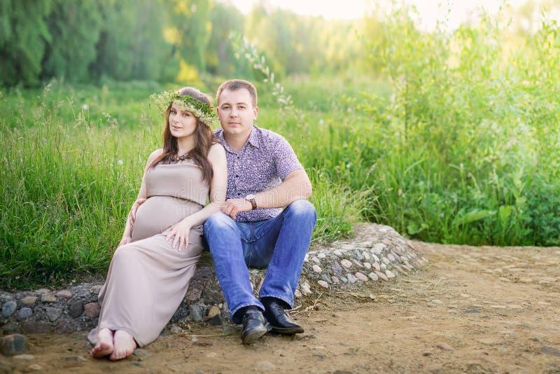 Une femme enceinte avec son mari s'asseyant sur la nature photographie stock libre de droits