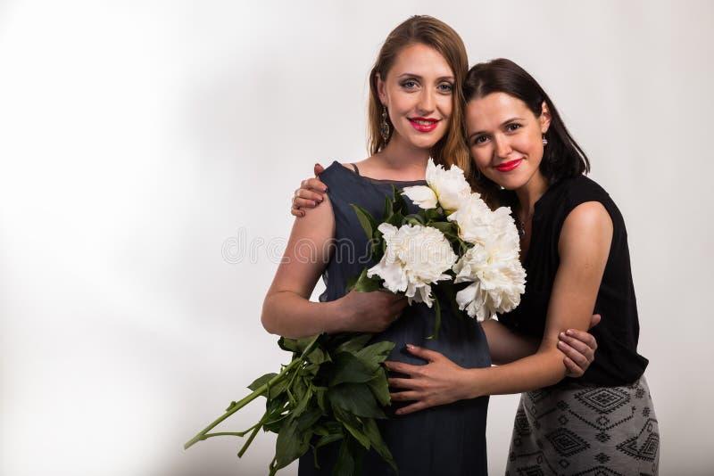 Une femme enceinte avec une amie sur un fond clair photo libre de droits