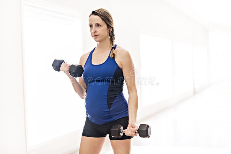 Une femme enceinte fait des exercices au gymnase images stock