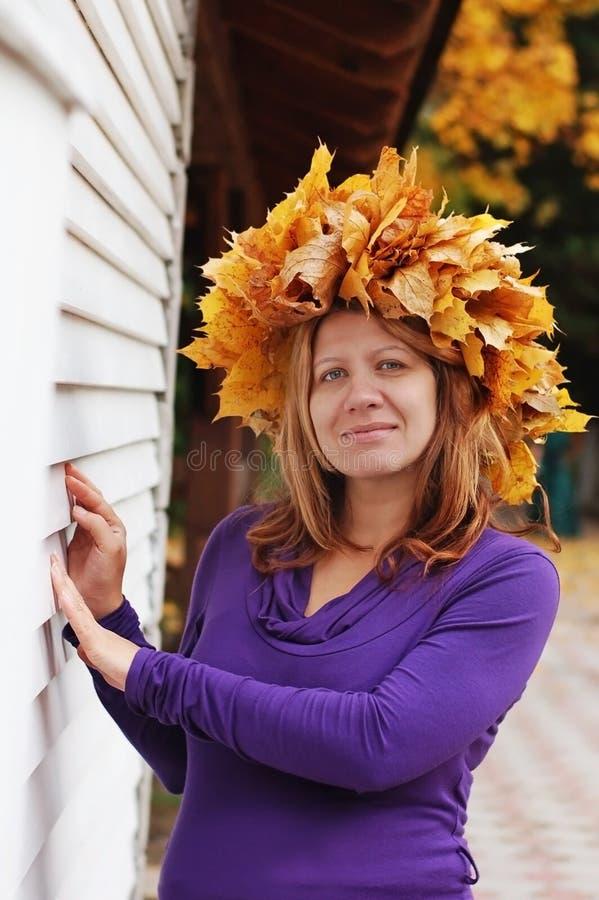 Une femme enceinte se repose en parc d'automne À la tête de sa guirlande tissée des feuilles d'automne image libre de droits