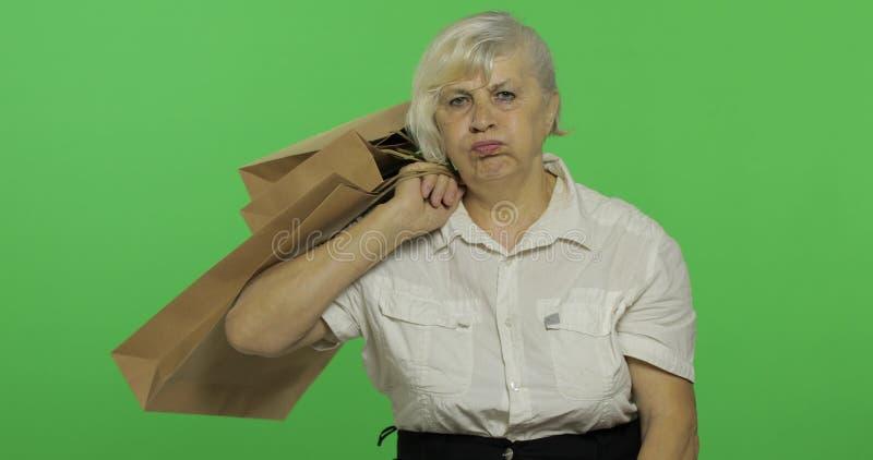 Une femme ennuyée pluse âgé avec des sacs à provisions Achats pr?sents Plan rapproch? photo libre de droits