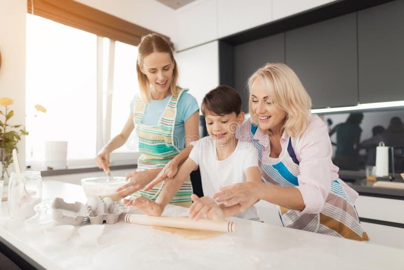 Une femme enseigne son fils à faire cuire les biscuits faits maison La grand-mère les aide Le garçon roule la pâte sur la table images stock