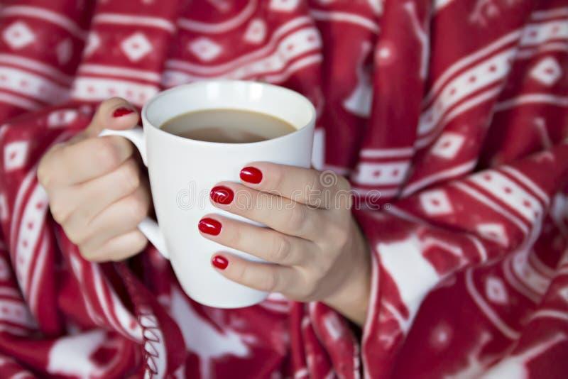 Une femme enveloppée dans une couverture avec une tasse de boisson chaude image libre de droits