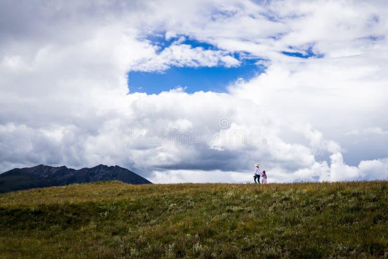 Une femme et une fille marchent par les prairies de Sichuan occidental image libre de droits