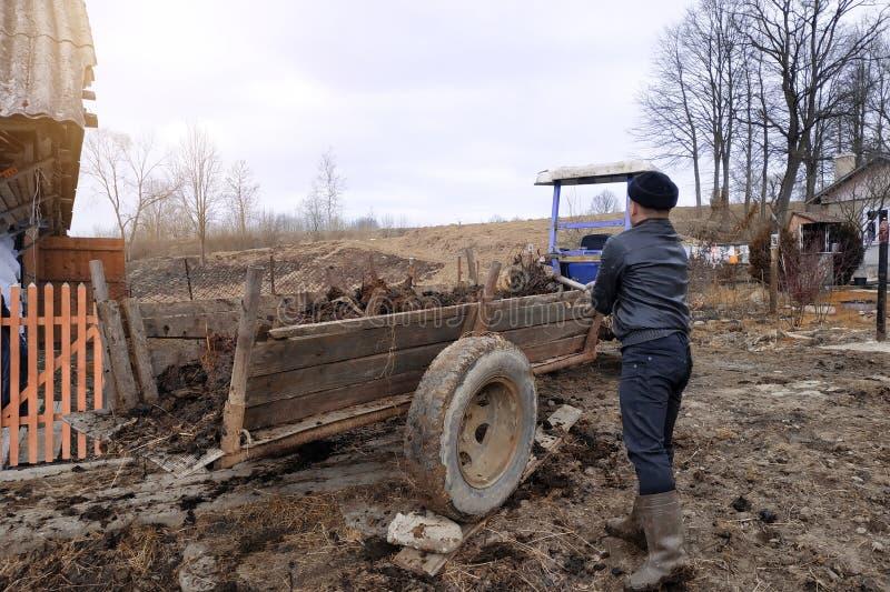 Une femme et un homme près de la grange pour des vaches choisissent l'engrais d'un puits pour fertiliser le sol dans le jardin, l photos stock