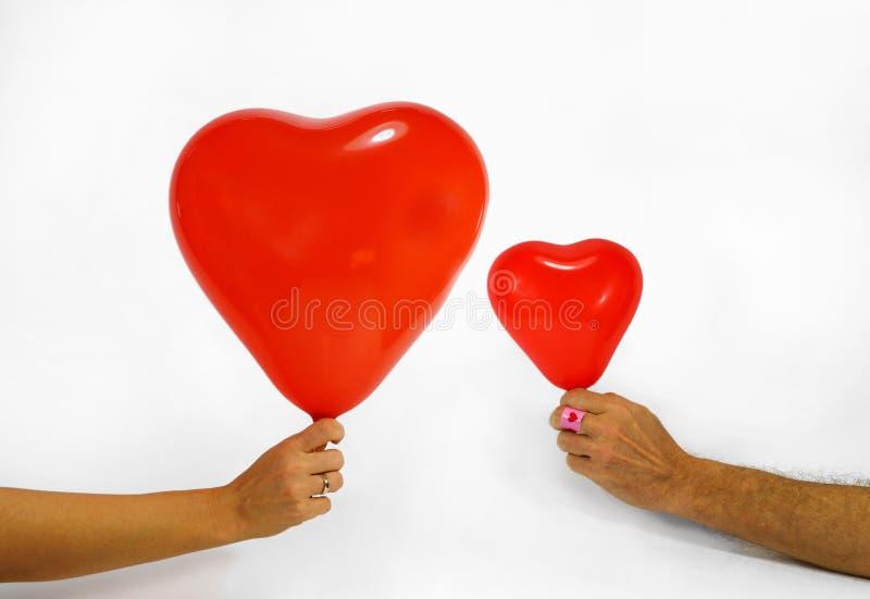 Une femme et un homme tiennent les ballons en forme de coeur dans leurs mains Jour du `s de Valentine images stock