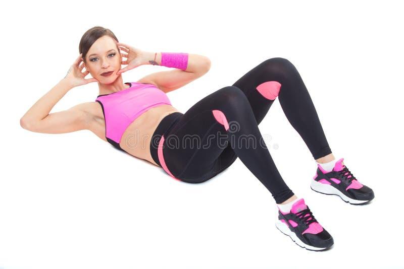Une femme exerçant les pousées abdominales d'exercice d'aérobic de forme physique de séance d'entraînement posent sur le fond bla photographie stock libre de droits