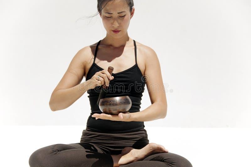 Une femme guérissante avec un bol de chant tibétain photos libres de droits