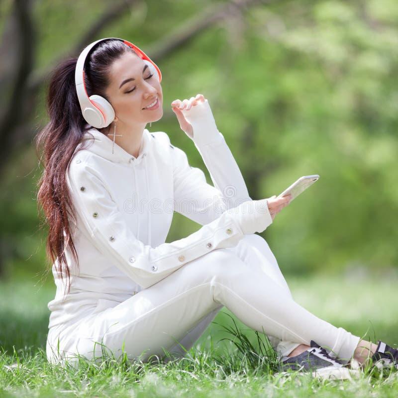 Une femme heureuse avec des écouteurs relaxants dans le parc Beauté paysage nature avec fond coloré Une femme de mode qui aime la photographie stock