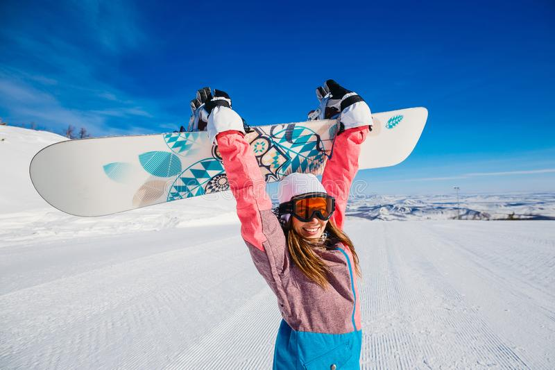 Une femme heureuse en costume et verres de ski tient un surf des neiges dans des ses mains image libre de droits