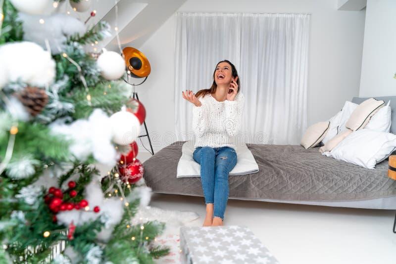 Une femme heureuse parlant au téléphone pendant Noël images stock