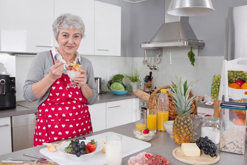 Une femme heureuse plus âgée mangeant du yaourt pendant le matin images libres de droits