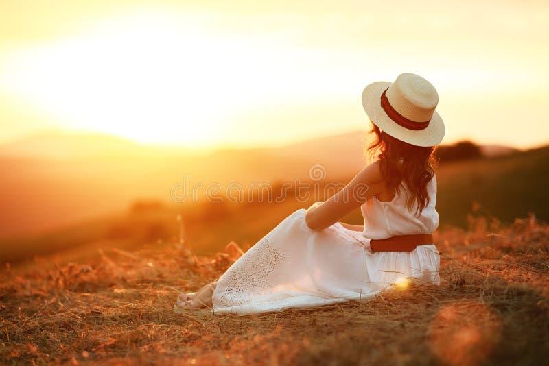Une femme heureuse se tenant le dos au coucher du soleil dans la nature images libres de droits
