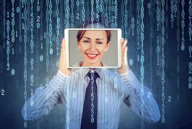 Une femme heureuse tenant une tablette avec son visage exposé sur un écran photos libres de droits