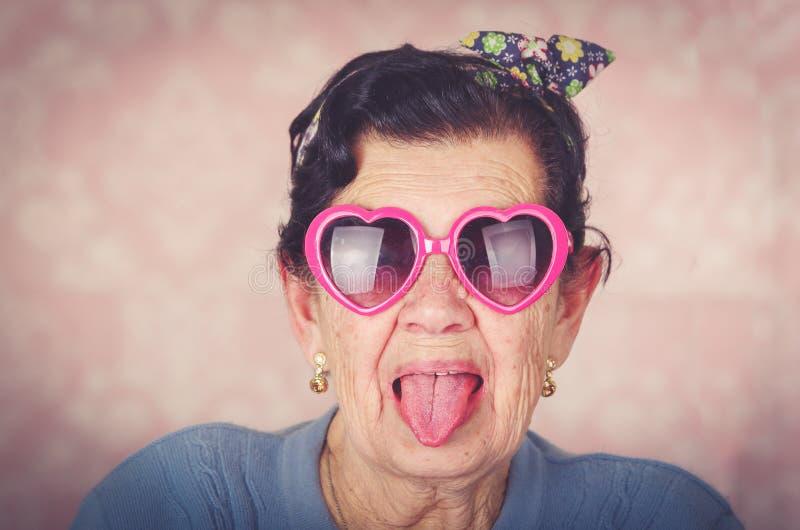 Une femme hispanique fraîche plus âgée portant le chandail bleu, l'arc de modèle de fleur sur les lunettes de soleil en forme de  image stock