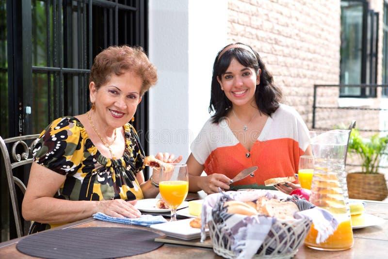 Une femme hispanique supérieure prenant le petit déjeuner dehors avec une fille photographie stock libre de droits