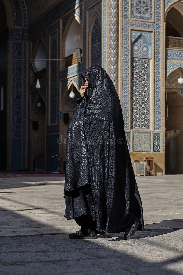 Une femme islamique dans une robe longue noire marche près de la mosquée image libre de droits