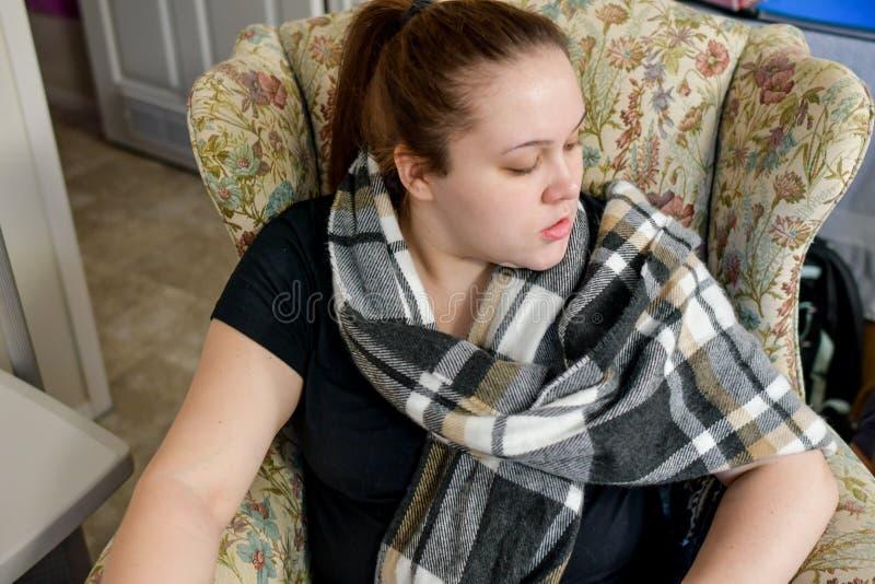 Une femme jette un coup d'oeil plus de dans un fauteuil jaune photographie stock libre de droits