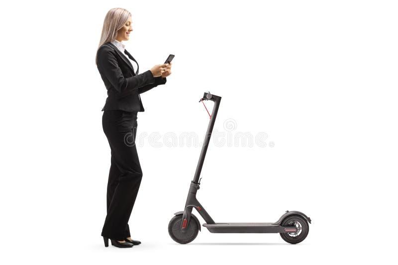 Une femme louant un scooter électrique avec une application de téléphone mobile images libres de droits