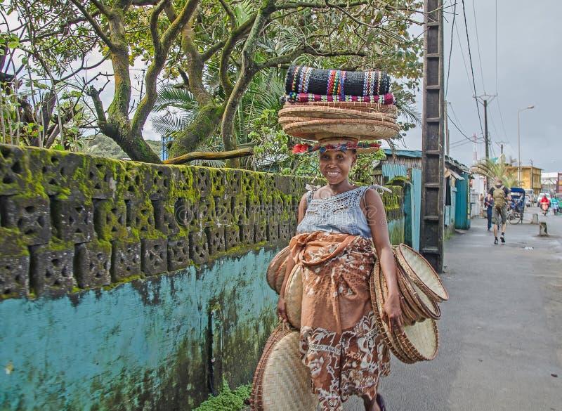 Une femme malgache indigène vend un certain travail manuel sur la rue photos stock