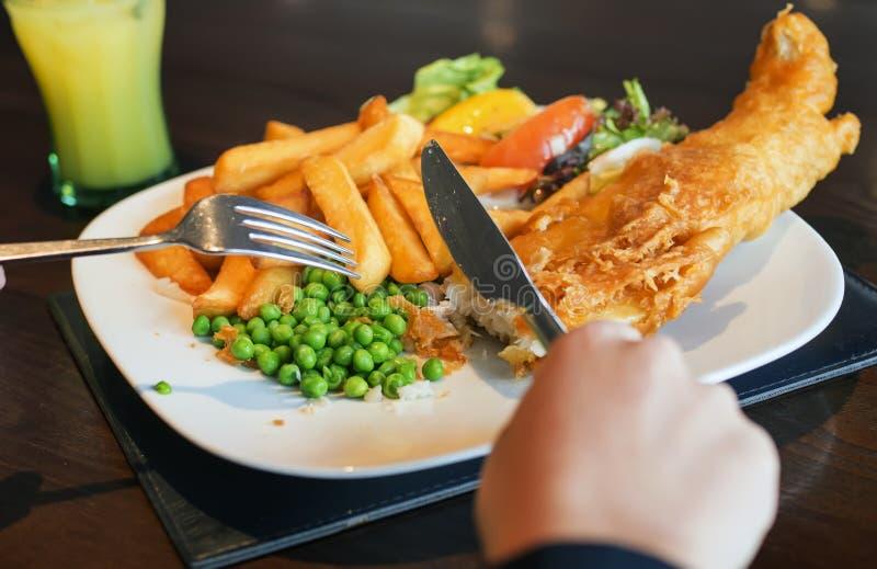 Une femme mangeant des poisson-frites photographie stock libre de droits