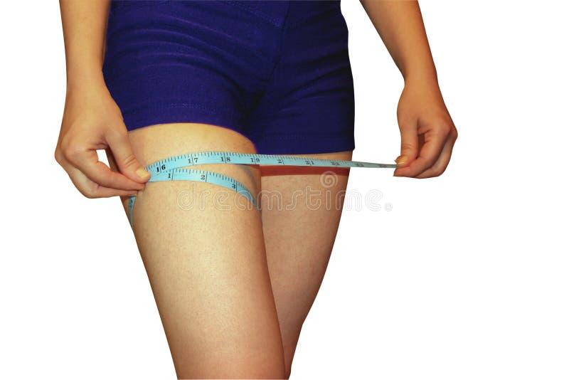 Une femme mesure une pièce de sa jambe, un régime de sport, un processus sain de la vie, fond blanc d'isolement image stock