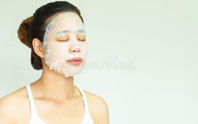 Une femme a mis le masque sur le visage pour le traitement photo stock