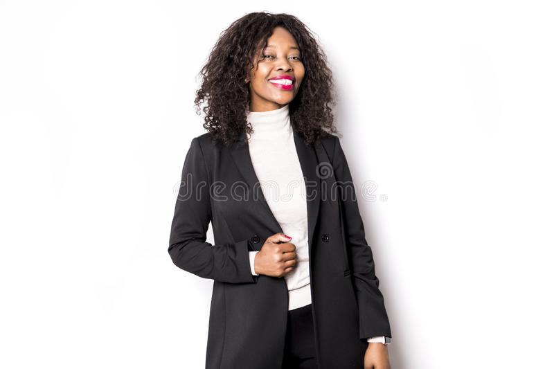 Une femme noire d'affaires pose pour un portrait sur le blanc de studio photo libre de droits