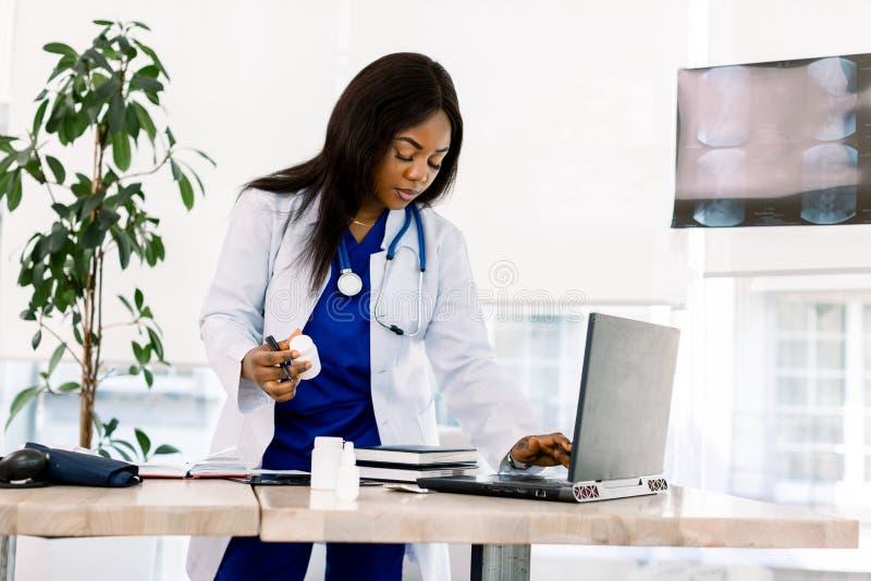 Une femme noire médecin se tient dans un bureau regardant un ordinateur portable, une infirmière afro-américaine travaille sur un images stock
