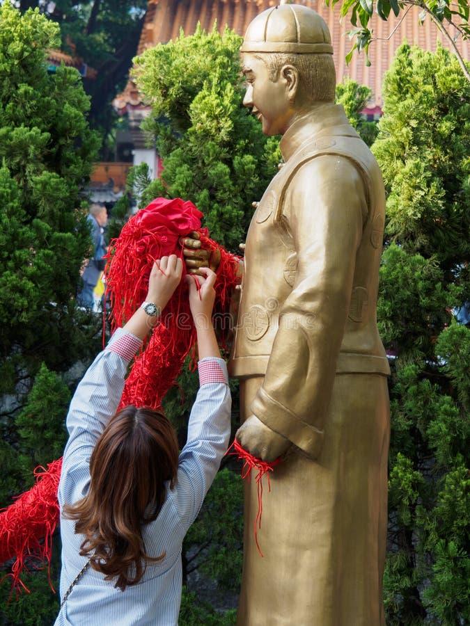 Une femme noue une corde rouge à la statue de Yue Lao chez le Wong Tai Sin Temple en Hong Kong photos stock