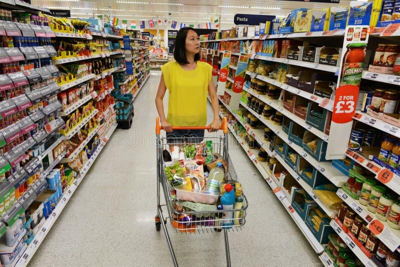Une femme passe en revue un bas-côté de supermarché images libres de droits