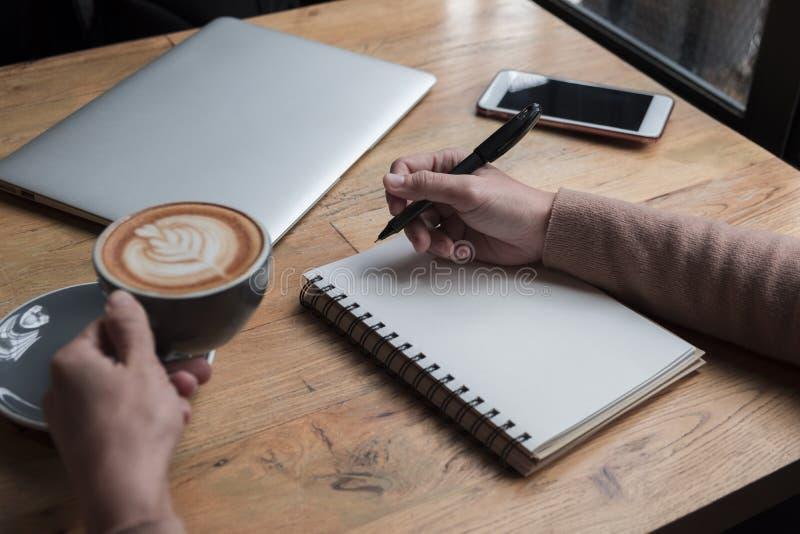 Une femme pense le concept d'affaires au bureau elle tenant une tasse outre du café sur la table ayez l'ordinateur portable et le photos libres de droits