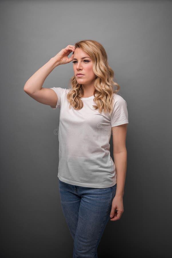 Une femme pense tenant sa t?te ou a un mal de t?te photographie stock