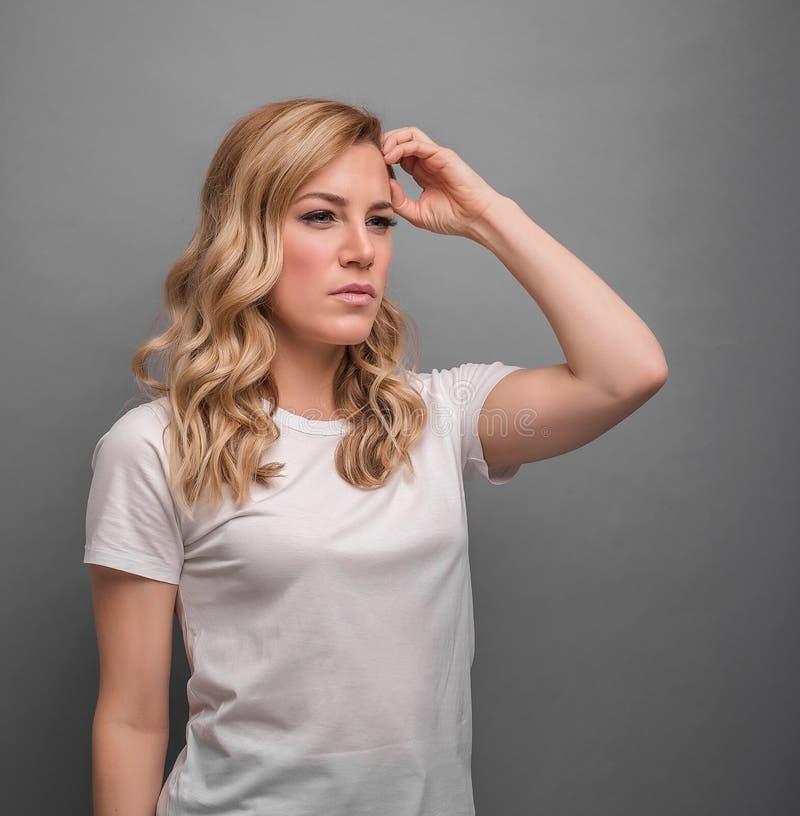 Une femme pense tenant sa t?te ou a un mal de t?te images stock