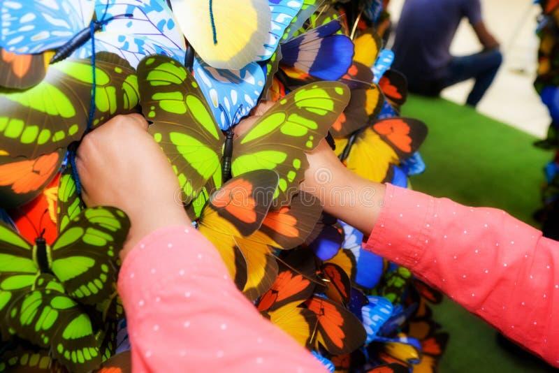 Une femme place les papillons colorés dans un arbre de papillon photos stock