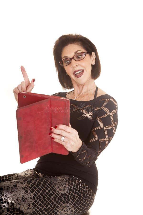 Une femme plus âgée avec le doigt de comprimé  photographie stock