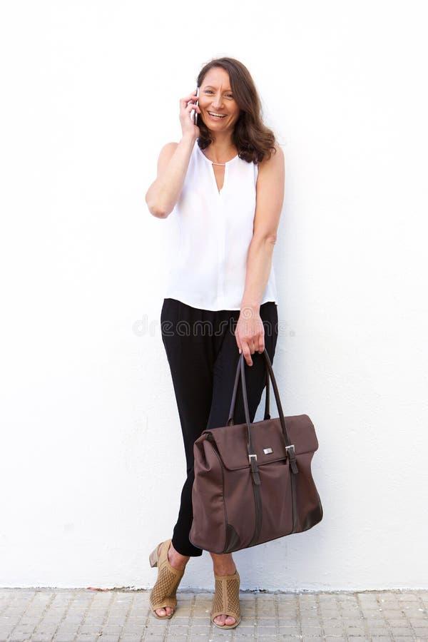Une femme plus âgée avec le sac parlant au téléphone portable photo libre de droits