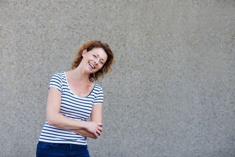 Une femme plus âgée avec les cheveux bouclés se tenant avec des bras croisés images libres de droits